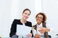 Two cheerful businesswomen working with documents together Royalty Free Stock Photo