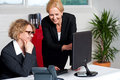 Two cheerful corporate women in office business working with colleague Royalty Free Stock Image