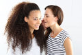 Two cheerful friend young women whisper in his ear Stock Photo