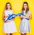 Two cheerful girlfriends beautiful girl holding hands on toy inflatable dolphin. Indoor. Royalty Free Stock Photo
