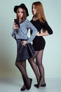 Two cheerful smiling sexy girl girlfriends photographed on the phone, do selfie phone in the studio on a gray background Royalty Free Stock Photo