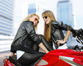 Two cheery motorcyclists and motorcycle Royalty Free Stock Image