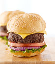 Two cheeseburgers on a wooden surface. Stock Images