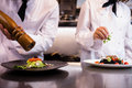 Two chefs garnishing meal on counter in commercial kitchen Stock Photo