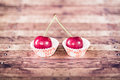 Two cherries on cupcake liners studio shot of inside brown wood background shallow depth of field and selective focus Stock Photos
