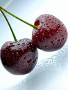 Two cherries with waterdrops on light blue surface Royalty Free Stock Photos