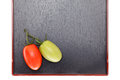 Two cherry tomatoes branch of the on black japanese square tray Royalty Free Stock Photos