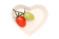 Two cherry tomatoes branch of the on heart shaped plate Royalty Free Stock Photo
