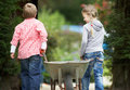 Two childen playing with wheelbarrow in garden walking away from camera Royalty Free Stock Photos