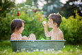 Two children, boy brothers, having a bath outdoors, making soap Royalty Free Stock Photo