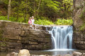 Two children boy and girl sitting near waterfall in forest Royalty Free Stock Photo