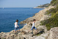 Two children, boys, running on rocks on the shore of the sea Royalty Free Stock Photo