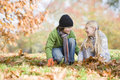 Two children collecting leaves Royalty Free Stock Photo