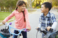 Two children on cycle ride in countryside smiling Stock Photos