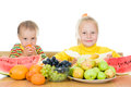 Two children eat fruit at a table Royalty Free Stock Image