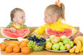 Two children eat fruit at a table Stock Photo
