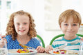 Two children eating meal at home together looking to camera smiling whilst holding knife and fork Stock Photography