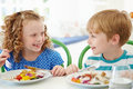 Two children eating meal at home together sitting down smiling each other Stock Images