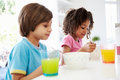 Two children having breakfast in kitchen together eating cereal Stock Photo