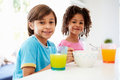 Two children having breakfast in kitchen together looking to camera smiling Stock Images