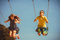 Two children having fun on swingset and joy of little girl and boy playing outdoor preschool playground garden kids swinging swing Stock Photo