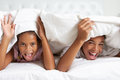Two children hiding under duvet in bed smiling to camera Royalty Free Stock Images