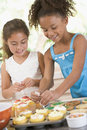 Two children in kitchen decorating cookies Royalty Free Stock Photo