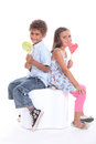 Two children with lollipops sat back to back Royalty Free Stock Image