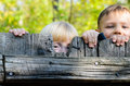 Two children peeking over a wooden fence Royalty Free Stock Photo