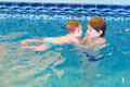 Two children playing in a swimming pool happy Stock Image