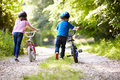 Two children pushing bikes along country track away from camera wearing helmets Stock Image