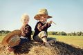 Two children sitting on hay bale in autumn young kids a little boy and his baby brother are top of a wearing straw hats a sunny Stock Image