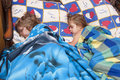 Two children sleep in rural bed of the the beds old rustic are covered with old blankets Royalty Free Stock Photos