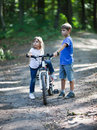 Two children stand with bicycle as they travel on forest Stock Photo