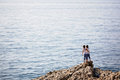 Two children, standing on rocks on the shore of the sea Royalty Free Stock Photo