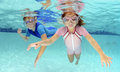 Two children swimming underwater in pool pink and blue Royalty Free Stock Photography