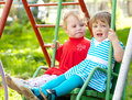 Two children on swing Stock Photo
