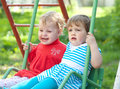 Two children on  swings Royalty Free Stock Image