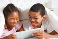 Two children using digital tablet under duvet smiling Stock Image