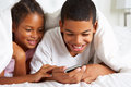 Two children using mobile phone under duvet smiling Royalty Free Stock Image