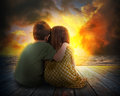 Two children watching summer sunset a little boy and girl are hugging and the in the sky the are sitting on wood for a family love Stock Image