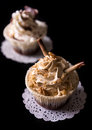 Two chocolate cupcakes with walnut and chocolate on black background Stock Photos