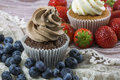 Two chocolate and vanilla cupcakes with blueberries and strawberries Royalty Free Stock Photo