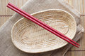 Two chopsticks next to a red and white basket Stock Image