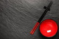 Two chopsticks and red plate on black stone background Royalty Free Stock Photo