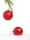 Two christmas balls one hanging frpm a tree and one in the snow Stock Photo