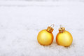 Two christmas balls on snow yellow Royalty Free Stock Image