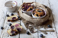 Two clafoutis with blueberries and cherries on ceramic ramekins and cake slices on rustic white vintage background Royalty Free Stock Photo