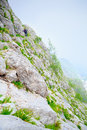 Two climbers climb a path carved into the sheer rock to reach top of mountain called altissimo in apuan alps of Stock Photography