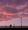 Two close people walking on a bridge in the evening under sunset sky with orange purple clouds Royalty Free Stock Image